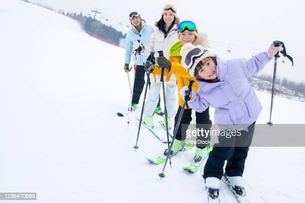ski ski field stood a row of happy family - ski resort stock pictures, royalty-free photos & images