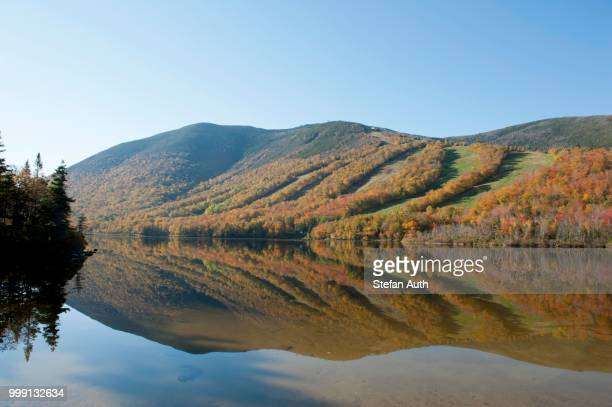 Ski slopes in autumn reflected in Profile Lake, foliage coloured during Indian Summer, Franconia Notch State Park, White Mountains National Forest, New Hampshire, New England, USA