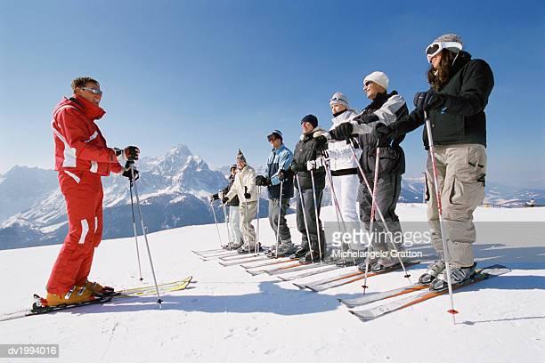 ski trainer with men and women on a ski slope - スキー板 ストックフォトと画像