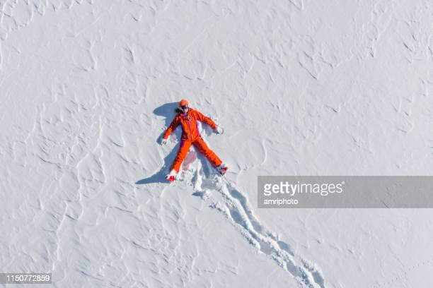 ski woman snow angel from above - snow angel stock photos and pictures