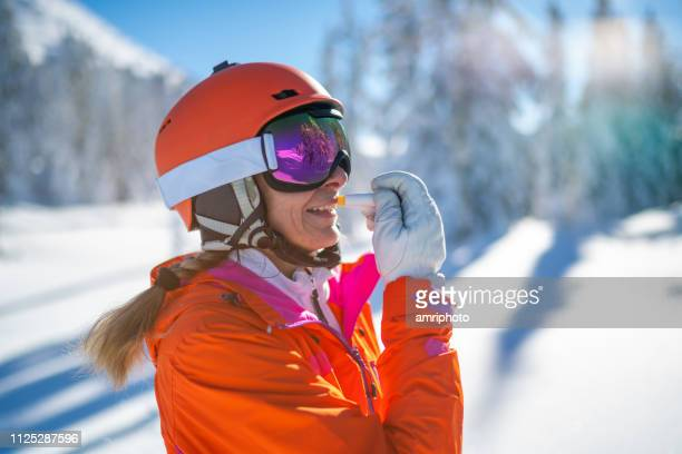 ski woman using sun protection lip gloss on sunny skiing day - lip balm stock pictures, royalty-free photos & images