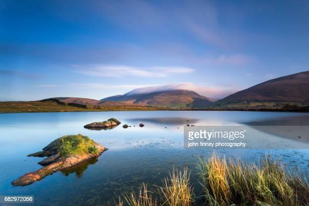 Skiddaw mountain from Tewit Tarn at sunrise. Lake District National park. UK.