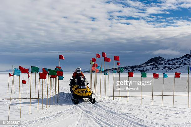 A skidoo carefully crosses a fuel pipe marked with flags on the Ross Ice Shelf.