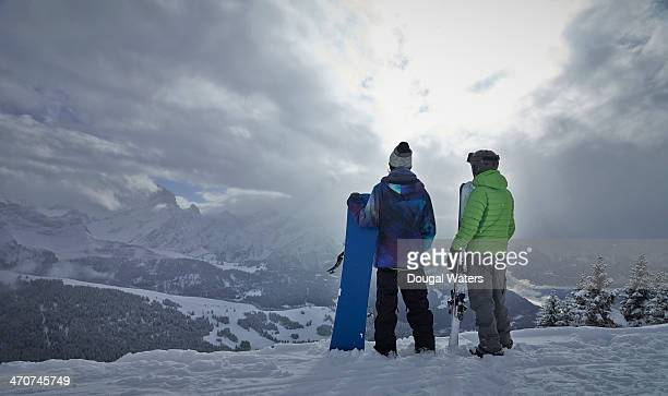 Skier and snowboarder look out over The Alps.
