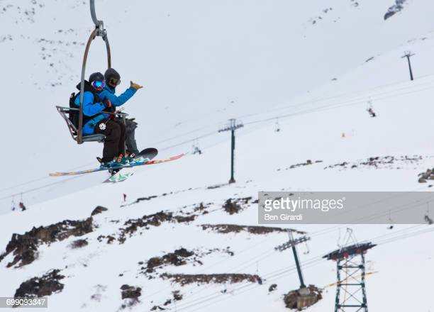 A Skier And Snowboarder Ride A Chairlift Together At Cerro Catedral In Argentina