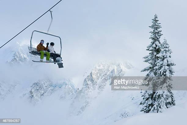 Skier and snowboarder riding lift