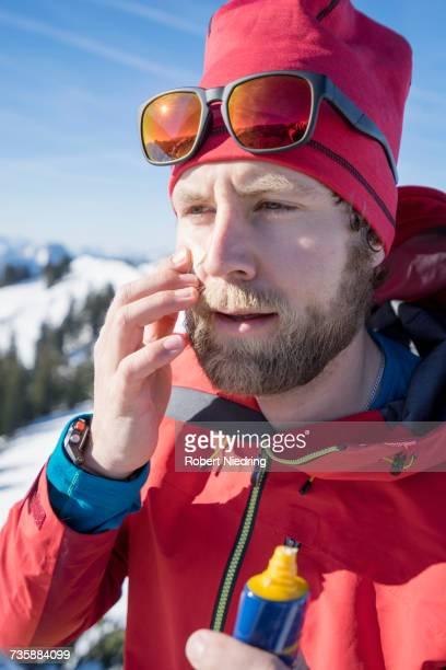 Skier applying sun cream on face