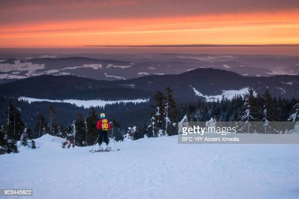 Skier ascends slope at daybreak, above mountains