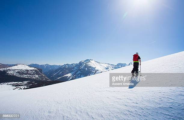 Skier ascends snowslope to mountain summit