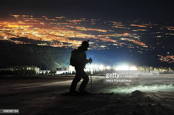 Skier at night over city lights