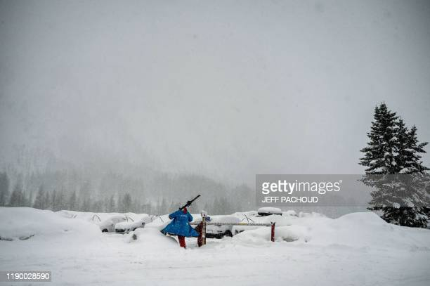 Skier carries his belongings while leaving the aera of the tracks of the Women's FIS Alpine ski World Cup on December 22 in Val d'Isere. - The races...