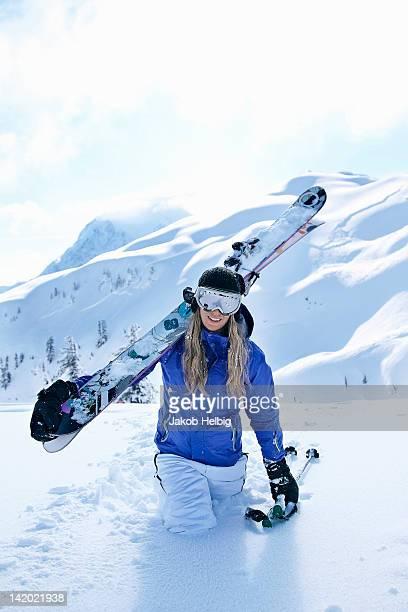 skier carrying skis in snow - diepe sneeuw stockfoto's en -beelden