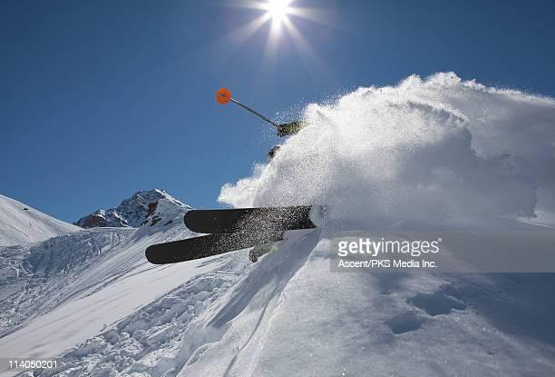 Skier carves turn on ridge crest, powder billow
