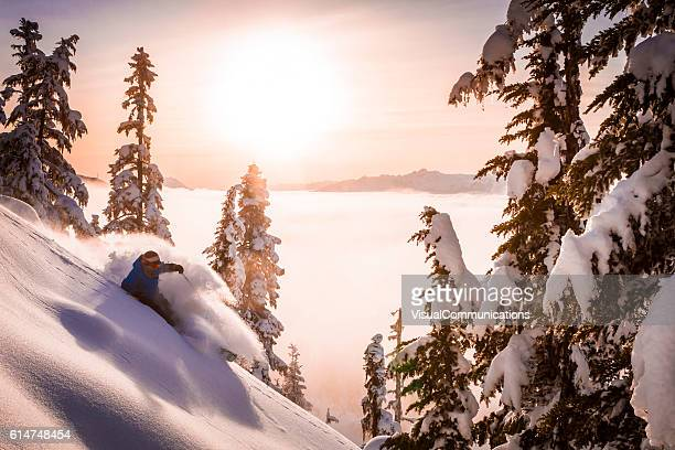 Skier carving fresh powder in sunset.