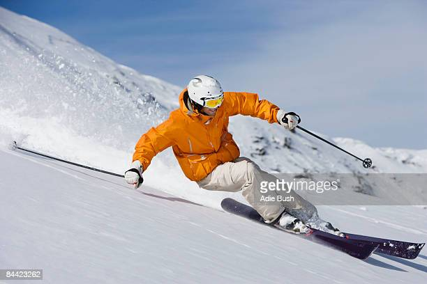 Skier carving through powder snow
