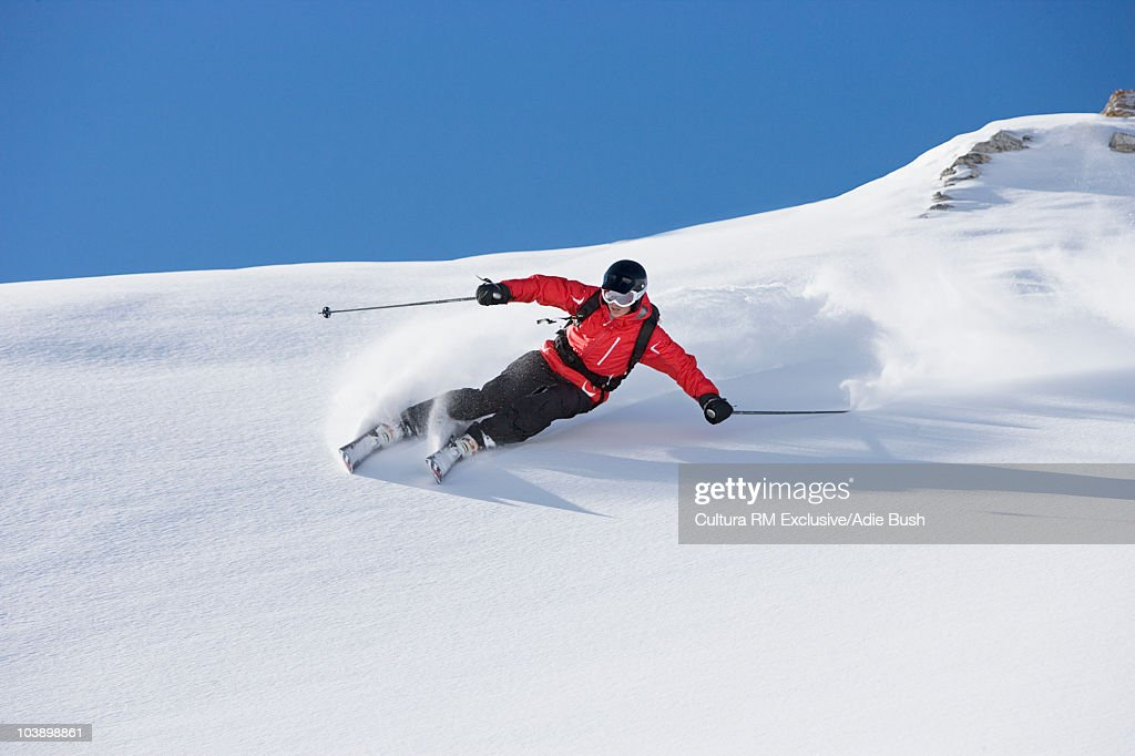 Skier carving turn through fresh powder : Stock Photo