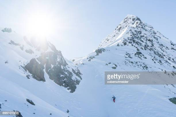 Skier climbing up a steep slope, Tirol, Austria