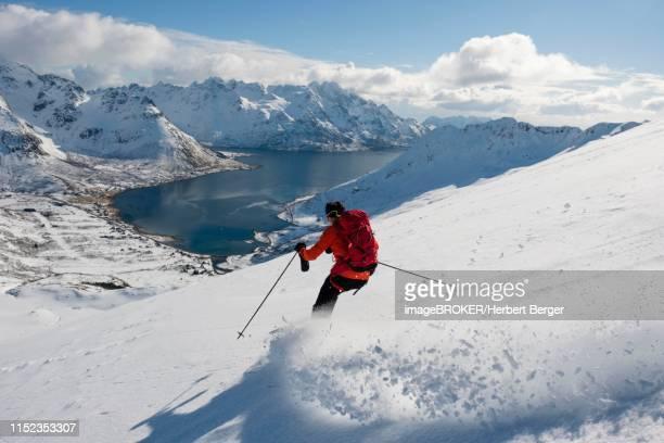 skier descending from pilan overlooking a fjord, austvagoey, lofoten, norway - lofoten stock pictures, royalty-free photos & images