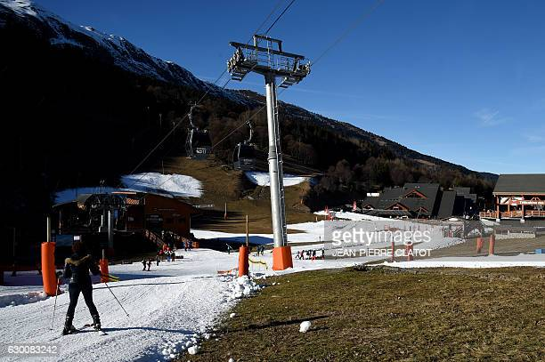A skier descends a slope where snow is sparse in the French ski resort of Meribel French Alps on December 16 on the eve of Christmas holidays in...
