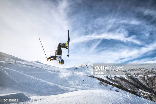 skier doing a backflip jump in alps ski resort, alpe di mera, piedmont, italy - stunt stock pictures, royalty-free photos & images