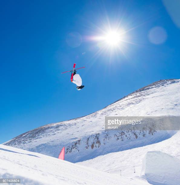 Skier doing high jumps in snowpark doing freestyle skiing day