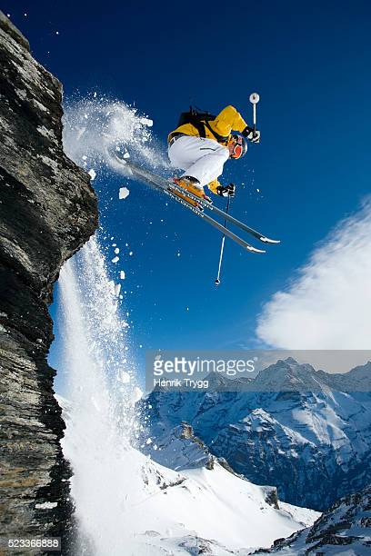 skier dropping cliff in swiss alps - ski jumping stock pictures, royalty-free photos & images