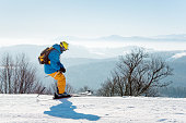 Skier enjoying skiing in mountains on a sunny winter day copyspace recreation active sport seasonal resort sportspeople adrenaline extreme concept