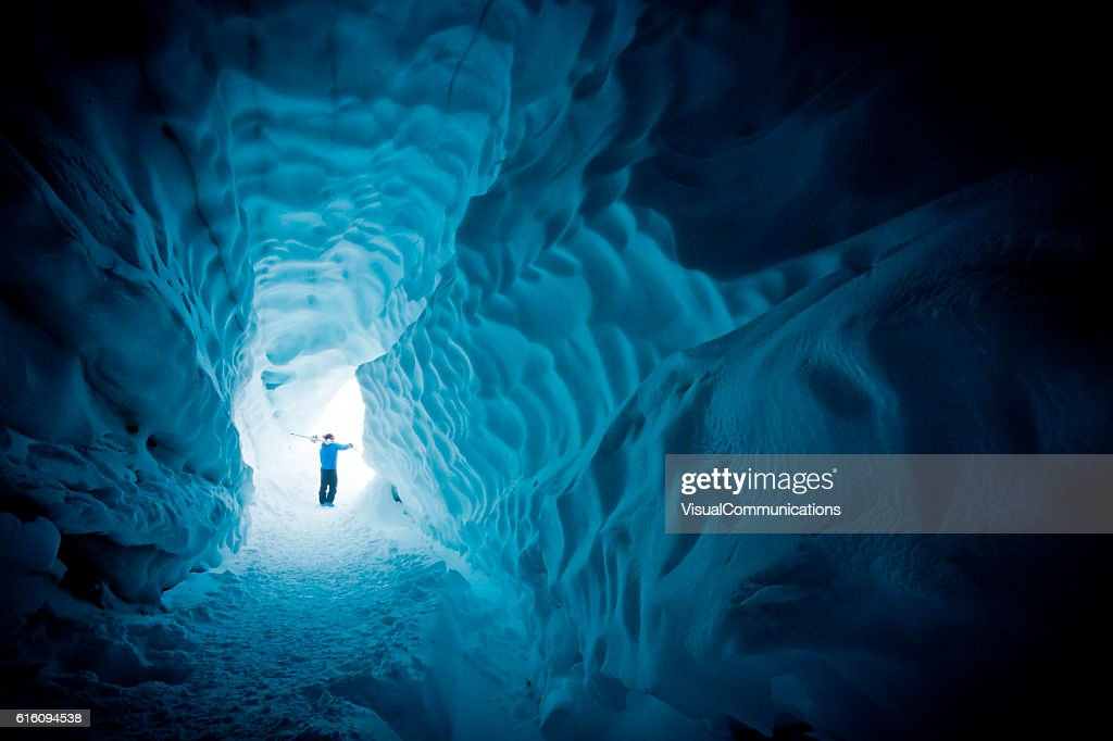 Skier exploring ice cave. : Stock Photo