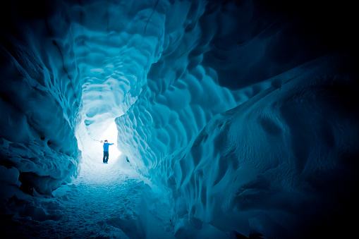 Skier exploring ice cave. 616094538