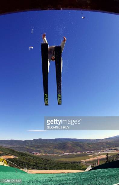 A skier flies through the air as water droplets fall off the edge of the K90 Jump during a summer joint USA / Canada training session at the Utah...