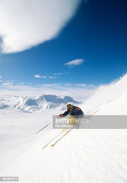 A skier going down a ski slope.
