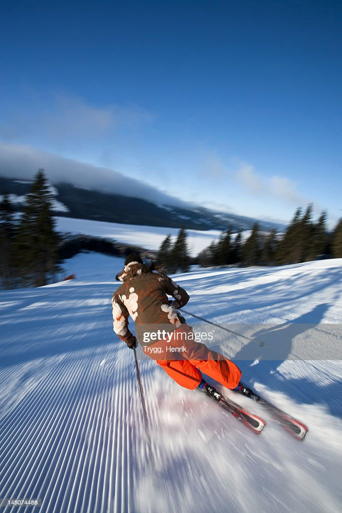 Skier going down slope, rear view : Stock Photo
