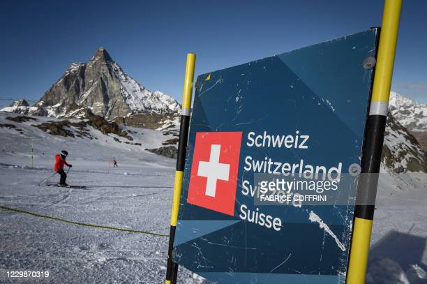Skier hits the slopes past a banner showing Swiss border above the ski resort of Zermatt in the Swiss Alps on November 28, 2020. - As EU countries...