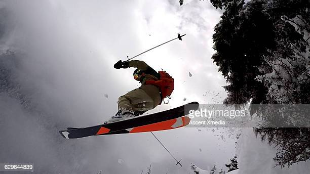 Skier in mid air flight over snow cliff, mountains