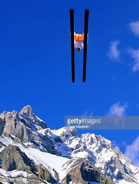 Skier in mid-jump, mountains in background (Digital Composite)