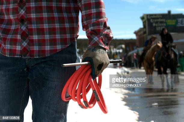 Skier Jason Dahl holds onto his baton and the rings he collected during his successful run down Harrison Avenue during the 68th annual Leadville Ski...