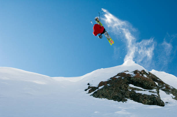 Skier jumping and doing a front flip in the backcountry terrain at Taos Ski Valley in New Mexico, USA
