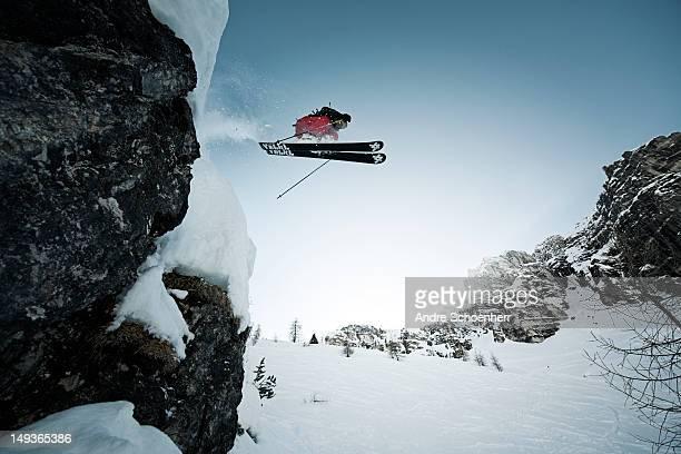 skier jumping of a cliff - skifahren stock-fotos und bilder