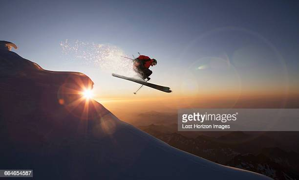 Skier jumping on a snowy slope at sunset, Zermatt, Canton Wallis, Switzerland