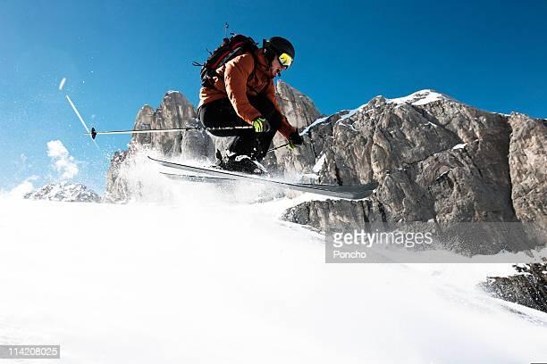Skier jumping over edge