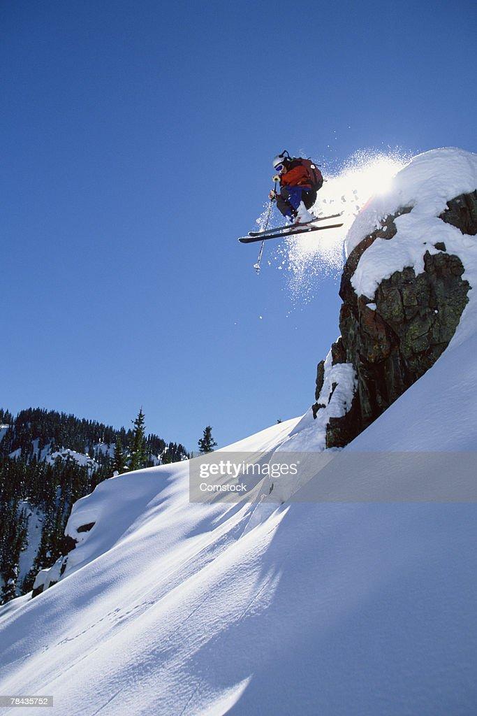 Skier jumping over ledge on mountain , Colorado : Stockfoto