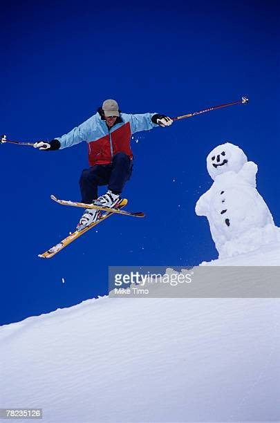 skier jumping with snowman in background - スキージャンプ ストックフォトと画像