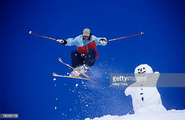 skier jumping with snowman in background - sport d'hiver photos et images de collection