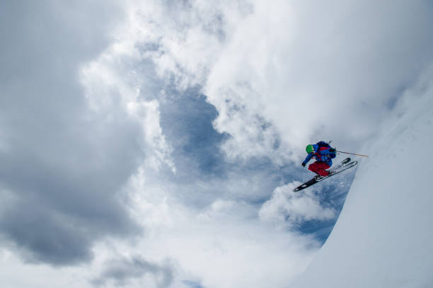 Skier jumps off of a cornice with lofty clouds behind