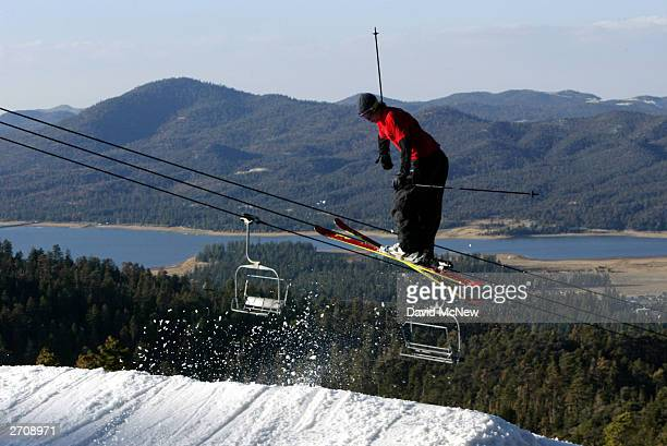 A skier jumps on an especially early opening day for the ski season at Big Bear Mountain with manmade snow as residents return from evacuation due to...