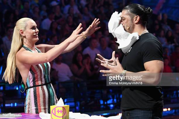 Skier Lindsey Vonn and WWE wrestler Roman Reigns participate in a challenge onstage during the Nickelodeon Kids' Choice Sports 2018 at Barker Hangar...