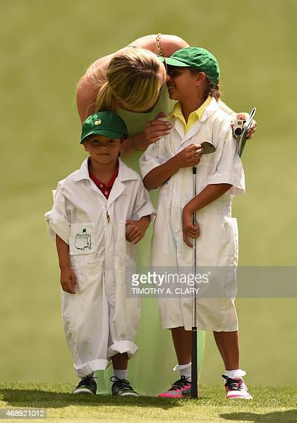 US Skier Lindsey Vonn kisses Sam Alexis Woods while standing with Charlie Axel Woods during the Par 3 competition on April 8 at Augusta National Golf...