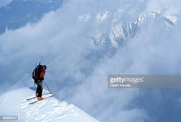 skier looking over cliff into clouds. - mont blanc massif stock photos and pictures