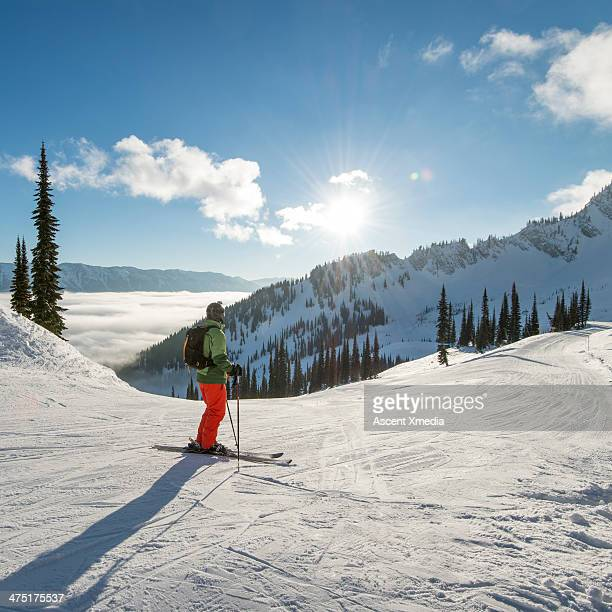 Skier looks off to distant mountains and sunrise