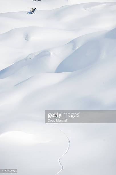 A skier makes his way down an alpine run to a waiting helicopter in the Selkirk Mountains, Canada.